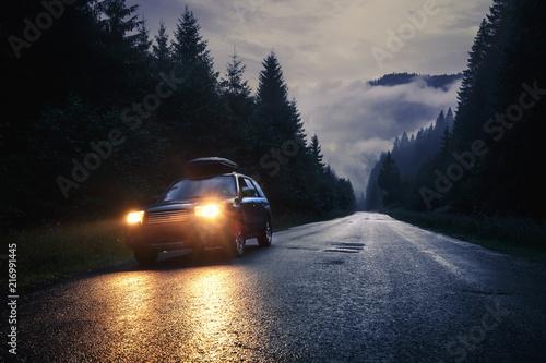 Obraz Car with headlights on at night road - fototapety do salonu