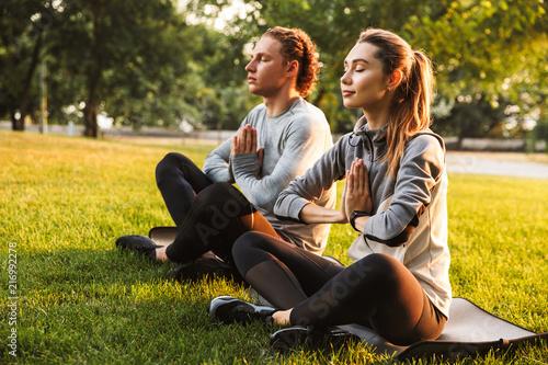 Obraz Fitness loving couple friends in park make meditate exercises. - fototapety do salonu
