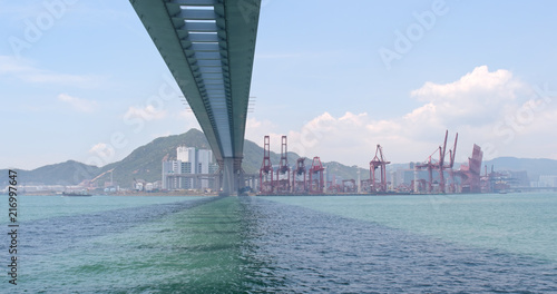 Foto op Aluminium Poort Cargo ship passing the harbor and Kwai Tsing Container Terminal in Hong Kong
