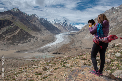 Photo Traveller woman with DSLR camera standing to take a beautiful landscpe image of D rang-Drung Glacier, Mountain glacier on zanskar road at Himalaya Range, Zanskar Range, Pensi La, Jammu and Kashmir