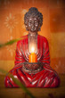 Buddha Zen statue holding a candle with warm orange light and bamboo leafsBuddha Zen statue holding a candle with warm orange light and bamboo leafs on a wooden natural surface
