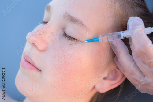 Portrait of a teenage girl doing an injection of botox