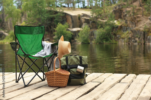 Set of camping equipment on wooden pier near lake