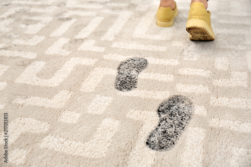 Obraz Person in dirty shoes leaving muddy footprints on carpet - fototapety do salonu
