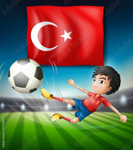 Fotobehang Kids Boy kicking a soccer ball infront of turkish flag