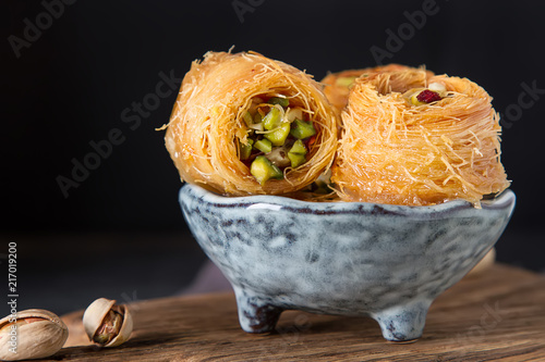 Deurstickers Dessert Traditional arabic dessert baklava with pistachios. Dark background
