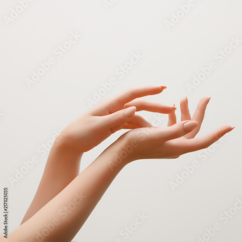 Cadres-photo bureau Manicure Closeup image of beautiful woman's hands with light pink manicure on the nails. Skin care for hands, manicure and beauty treatment. Elegant and graceful hands with slender graceful fingers