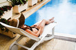 A beautiful girl in a straw hat lies on a lounger by the pool at the hotel sunbathing