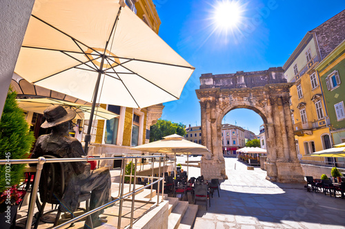 Foto  Street of Pula with historic Roman Golden gate and James Joyce statue view