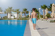 European boy walking along swimming pool. Back view.