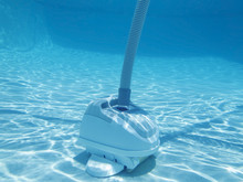 Underwater View Of Vacuum Cleaning Bottom Of Swimming Pool.