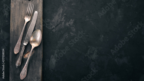 Fototapeta Old cutlery. On a black stone background. Top view. Free space for text. obraz