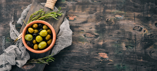 Olives in a plate and rosemary. On a black wooden background. Free space for text.
