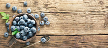 Freshly Picked Blueberries On Rustic Aged Wooden Table Surface. Flat Lay. Ripe Blueberry With Leaves In Ceramic Jar And Also Scattered Around  With Copy Space.