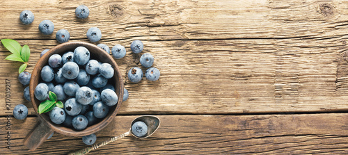 Fotografia Freshly picked blueberries on rustic aged wooden table surface