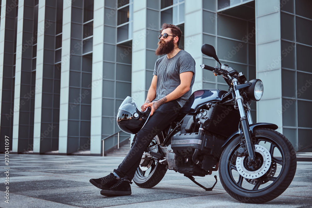 Fototapeta Brutal bearded male in a gray t-shirt and black pants holds a helmet sitting on his custom-made retro motorcycle against skyscraper.