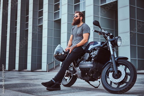 Fototapeta Brutal bearded male in a gray t-shirt and black pants holds a helmet sitting on his custom-made retro motorcycle against skyscraper