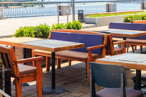 Fototapeta Chairs and tables in cozy outdoor cafe at summer obraz na płótnie