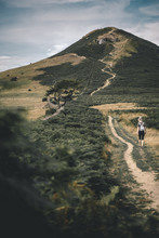 Woman Walking Towards A Hill