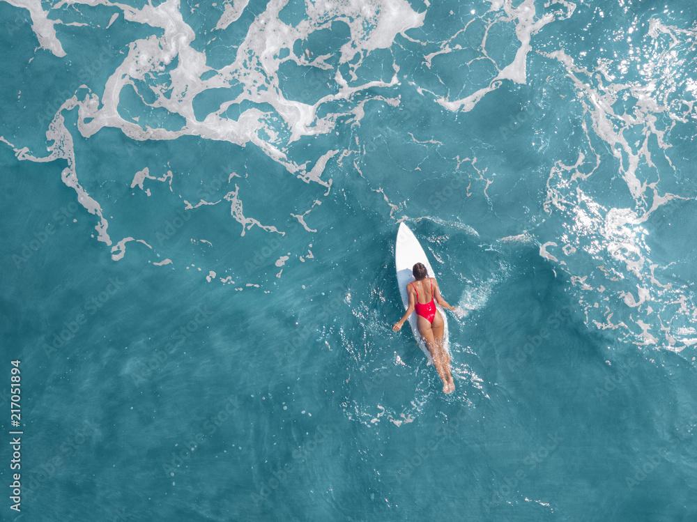 Fototapeta Surfer girl on surfboard in blue ocean, aerial view