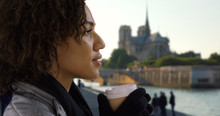 Close Up Of Cute Black Female Sipping Coffee And Looking Around Near Notre Dame