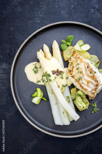 Modern German fried cod fish filet with white asparagus in hollandaise sauce with roast potatoes and sliced zucchini as top view on a plate with copy space