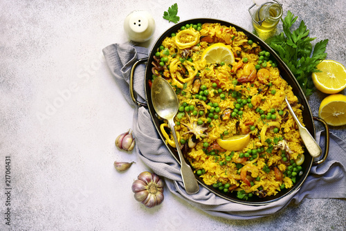 Classic valencian paella from rice with seafood and green pea - traditional dish of spanish cuisine.Top view with copy space.