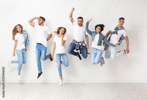 Photographie Group of young people in jeans jumping near light wall
