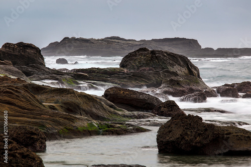 Foto op Plexiglas Kust Taiwan East Coast Rocky Coastline Background Image - Pure White Overcast Skies, Exotic Rock Formations in the shape of an ocean wave , Calm Water in the Foreground. Ocean Coastline