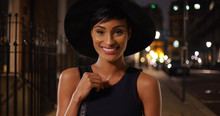 Young Attractive Black Female In Urban Setting Posing With Her Purse And Hat