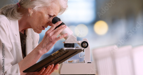 Fotografia  Mature female scientist takes notes on tablet computer and uses microscope