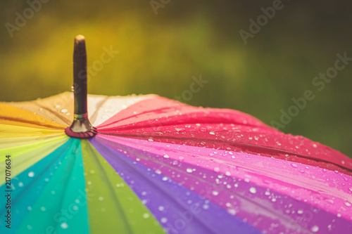 Surface of rainbow umbrella with raindrops on it. Close up, copy space.