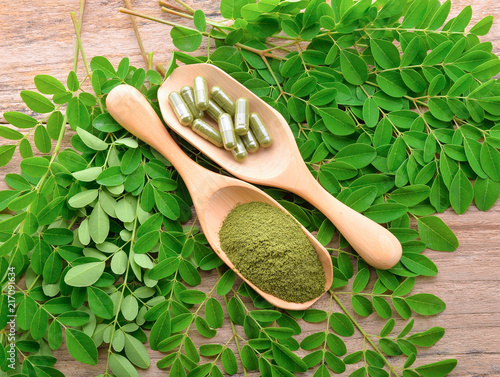 Stampa su Tela  moringa leaf and powder capsule on wooden background