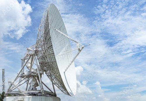 Big large white satellite dish turn up skyward on blue sky in earth communication antenna system center station