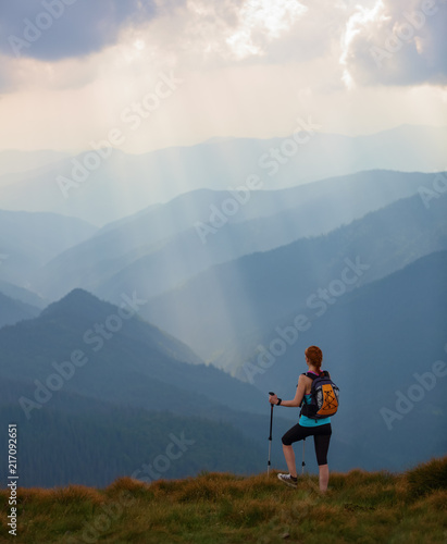 Foto op Canvas Diepbruine The view with the high mountains in fog. The sun rays are enlighten the forests. The extreme girl with the tracking sticks and back sack is staying on the lawnand watching the nature. Summer scenery.