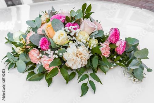 Photo bouquet de mariée sur capot de voiture blanche