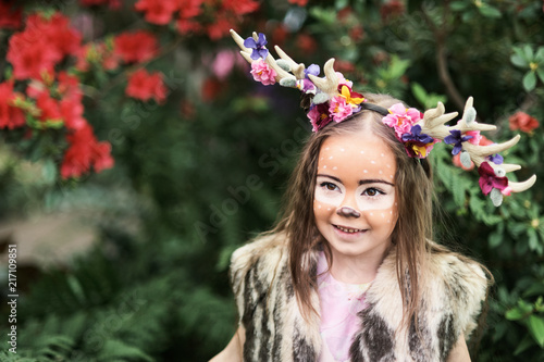 Canvas Prints Textures Fairy tale girl. Portrait a little girl in a deer dress with a painted face in the forest. Big antler. Fantasy girl. Springtime.