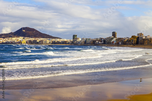 Las-Palmas de Gran Canaria, Spain, on January 10, 2018. The winter sun lights the Playa de Las Canteras beach on the bank of the Atlantic Ocean. beautiful embankment in the distance