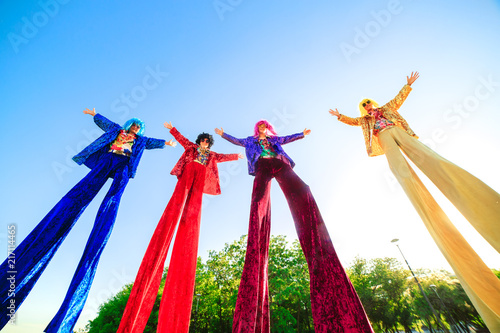 Young people on stilts posing against the blue sky. Fototapet