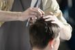 man getting haircut at barber shop. Hairdresser cutting hair of customer at salon.