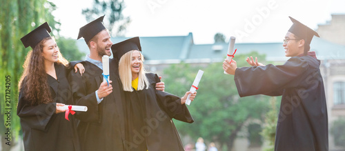 Photo portrait of happy multiracial graduates with diplomas on street