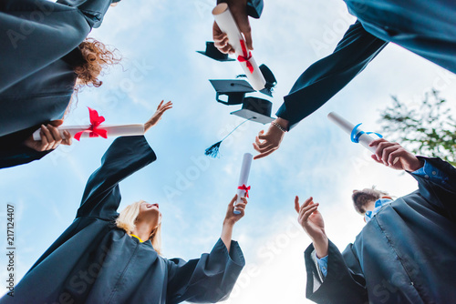 Fotografering bottom view of happy multicultural graduates with diplomas throwing caps up with