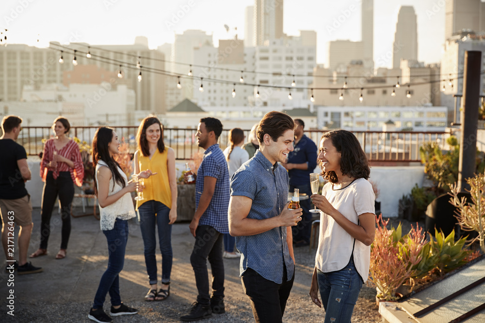 Fototapety, obrazy: Friends Gathered On Rooftop Terrace For Party With City Skyline In Background