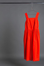 Red Summer Dress Hanging On A Hanger On A Gray Background, Concept Of Fashionable Clothes And Shopping