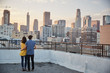 Rear View Of Couple On Rooftop Terrace Looking Out Over City Skyline At Sunset