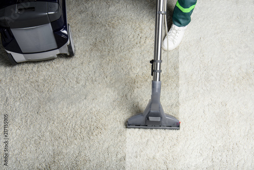 Fototapeta high angle view of person cleaning white carpet with professional vacuum cleaner
