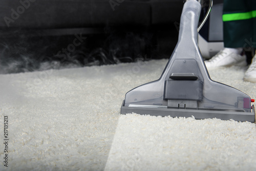 close-up view of person cleaning white carpet with professional vacuum cleaner Fotobehang