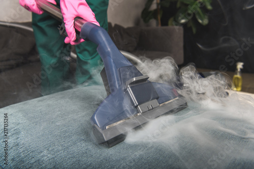 Fototapeta cropped shot of person cleaning sofa with vacuum cleaner, hot steam cleaning concept obraz