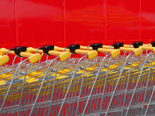 Stack Of New Shiny Shopping Carts In A Supermarket With Red Wall In Background