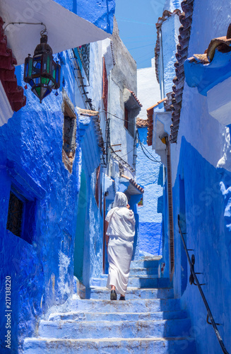 Poster Maroc Woman with white djellaba walking the blue streets of Chefchaouen, Morocco.
